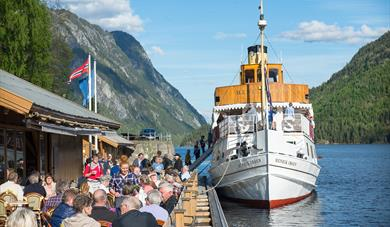 Lastein Brygggekafe and MS Henrik Ibsen which is located on a pier in Dalen